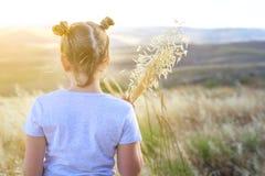 拿着燕麦的麦子和耳朵的钉美女 后面秋天领域的看法漂亮的孩子准备好收获 免版税库存图片
