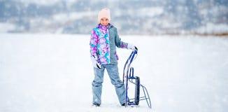拿着爬犁的滑雪服装的女孩 图库摄影