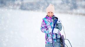 拿着爬犁的滑雪服装的女孩 免版税图库摄影