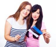 拿着爱沙尼亚语旗子的两个微笑的女孩 免版税库存图片