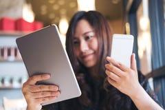 拿着片剂个人计算机和巧妙的电话的一个美丽的亚裔女商人,当工作时 免版税库存图片