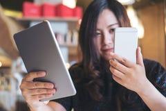 拿着片剂个人计算机和巧妙的电话的一个美丽的亚裔女商人,当工作时 图库摄影