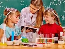 拿着片剂个人计算机的孩子和老师 免版税库存图片