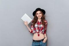 拿着片剂个人计算机的帽子和格子花呢上衣的偶然女孩 免版税图库摄影