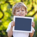 拿着片剂个人计算机的微笑的愉快的小孩,户外 免版税库存照片