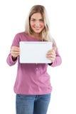 拿着片剂个人计算机的微笑的白肤金发的妇女 免版税库存照片