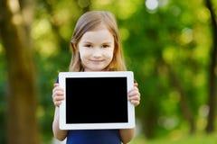 拿着片剂个人计算机的愉快的孩子户外 免版税库存照片
