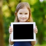 拿着片剂个人计算机的愉快的孩子户外 免版税图库摄影