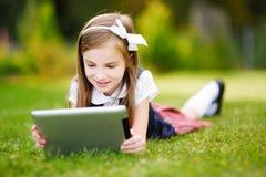 拿着片剂个人计算机的愉快的小女孩户外在夏天公园 库存图片