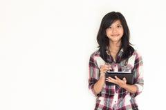 拿着片剂个人计算机的愉快的新亚裔女孩 图库摄影