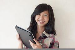 拿着片剂个人计算机的愉快的新亚裔女孩 免版税库存照片