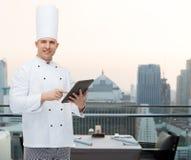 拿着片剂个人计算机的愉快的男性厨师厨师 库存照片