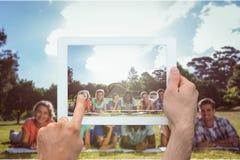 拿着片剂个人计算机的手的综合图象 库存照片