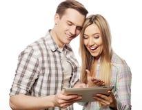拿着片剂个人计算机计算机的愉快的年轻夫妇 免版税库存图片
