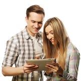 拿着片剂个人计算机计算机的愉快的年轻夫妇 免版税库存照片