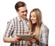 拿着片剂个人计算机计算机的愉快的年轻夫妇 库存图片