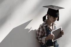 拿着片剂和商品的儿童女孩是有vint的一个学士帽子 免版税库存照片