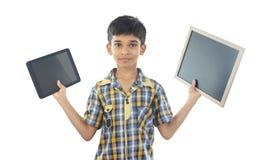 拿着片剂和板岩的印地安男孩 免版税库存图片