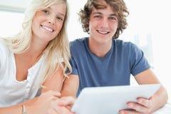 拿着片剂和查看照相机的一对微笑的夫妇 免版税库存照片