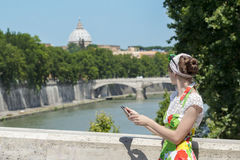 拿着片剂和看罗马台伯河桥梁和杰作圆顶的花sundress的旅游妇女 库存照片