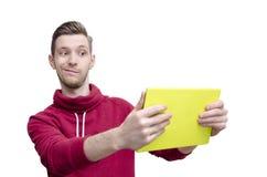 拿着片剂垫和看屏幕的可笑的年轻人 免版税库存照片