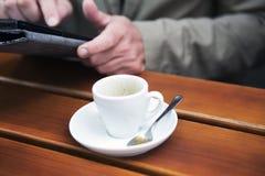 拿着片剂的人特写镜头和与咖啡 免版税库存图片