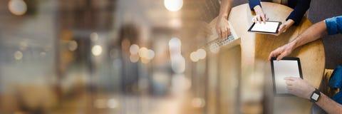 拿着片剂的商人开与被弄脏的光转折作用的一次会议 免版税库存照片