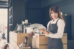 拿着片剂的小企业主在咖啡店的柜台 f 免版税库存图片