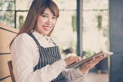 拿着片剂的小企业主在咖啡店的柜台 f 库存图片