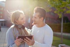 拿着片剂的年轻白种人夫妇户外在日落 免版税库存照片