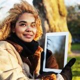 拿着片剂的年轻逗人喜爱的白肤金发的非裔美国人的女学生  免版税库存照片