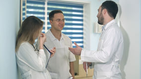 拿着片剂的男性医生谈与两其他医生在医院大厅里 免版税图库摄影