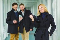 拿着片剂的白肤金发的女实业家注视着在您与同事的大厅的背景 免版税图库摄影