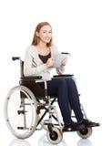 拿着片剂的轮椅的少妇 库存照片