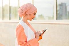 拿着片剂的阿拉伯女实业家画象 妇女在abaya打扮 免版税库存图片
