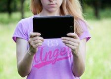 拿着片剂的年轻白肤金发的妇女户外 库存图片