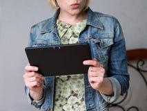 拿着片剂的年轻白肤金发的妇女 免版税库存图片