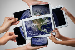 拿着片剂计算机和手机的手 库存照片