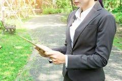 拿着片剂计算机有庭院背景的女商人 免版税库存图片