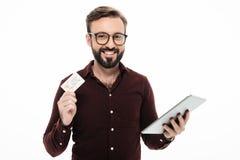 拿着片剂计算机的一个微笑的愉快的人的画象 免版税库存照片