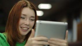 拿着片剂计算机的少妇,看屏幕和微笑,称某事 股票视频