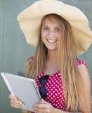 拿着片剂计算机的帽子的美丽的女孩手中 库存照片