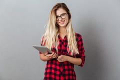 拿着片剂计算机的快乐的年轻白肤金发的妇女 免版税库存图片