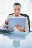 拿着片剂计算机的被聚焦的老练女实业家 免版税库存照片