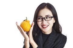 拿着牙买加丑橘的愉快的幼小亚洲企业经营者 免版税图库摄影