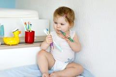拿着牙刷和刷第一颗牙的小女婴 学会的小孩清洗乳齿 库存图片