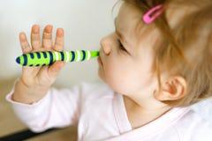拿着牙刷和刷第一颗牙的小女婴 学会的小孩清洗乳齿 免版税图库摄影