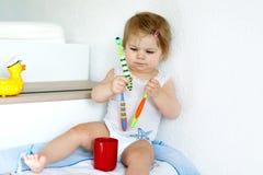 拿着牙刷和刷第一颗牙的小女婴 学会的小孩清洗乳齿 免版税库存图片