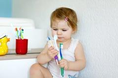 拿着牙刷和刷第一颗牙的小女婴 学会的小孩清洗乳齿 免版税库存照片