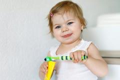 拿着牙刷和刷第一颗牙的小女婴 学会的小孩清洗乳齿 库存照片